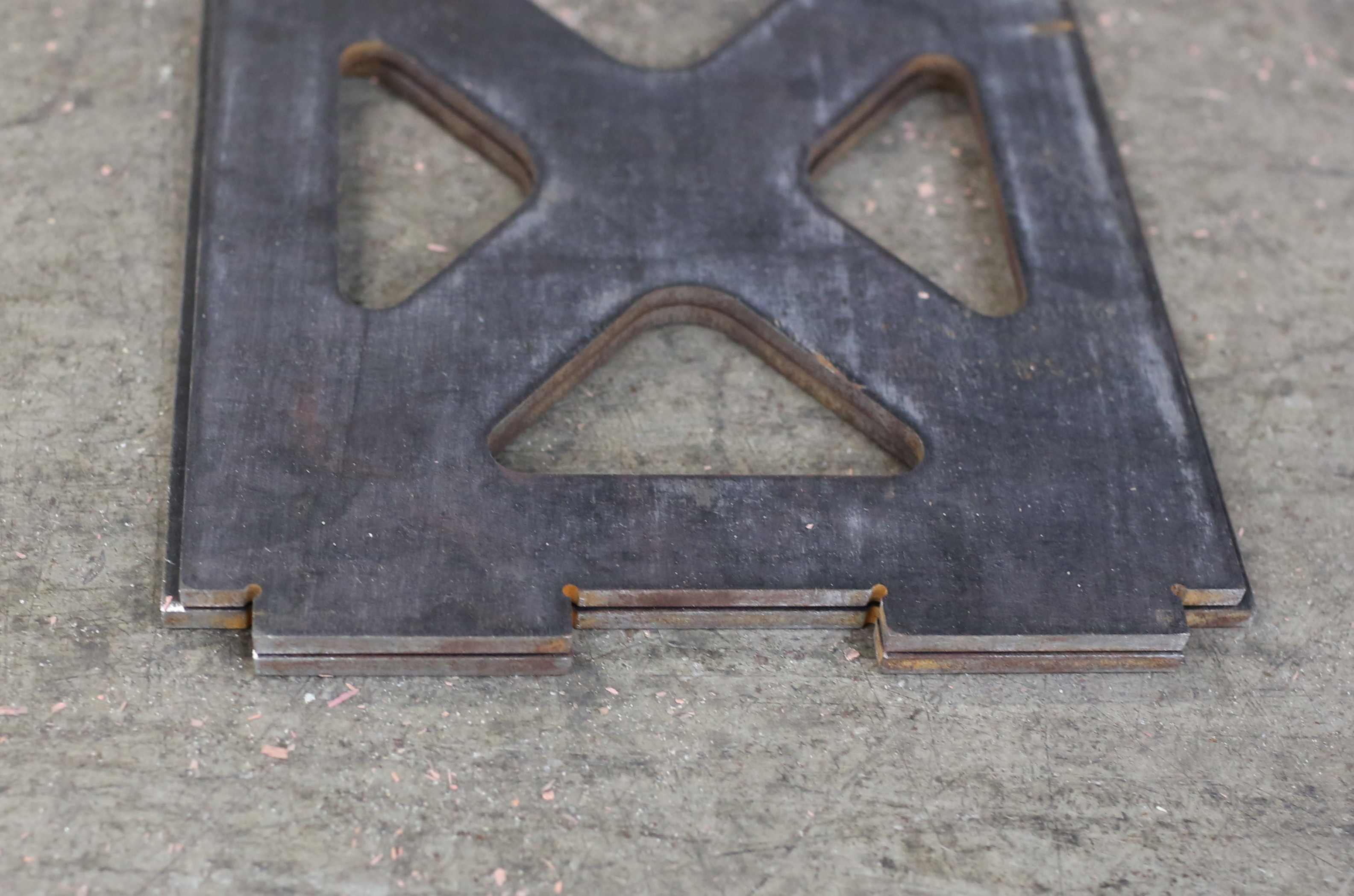Two nearly-identical stacked plates with the tabs aligned, highlighting the fact that they are slightly different sizes.